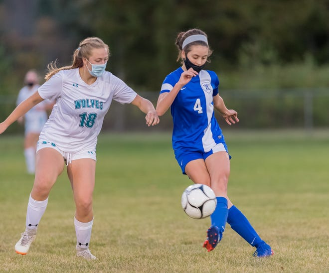 Alfred-Almond's Maeve Looney (4) looks to pass around Arkport/Canaseraga's Alyssa Greunke Friday night in Almond.
