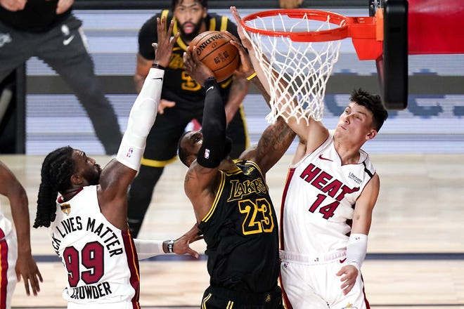 Los Angeles Lakers forward LeBron James scores between Miami Heat forward Jae Crowder and guard Tyler Herro (from left) during the second half in Game 5 of the NBA Finals Friday in Lake Buena Vista, Florida. [JOHN RAOUX / AP]