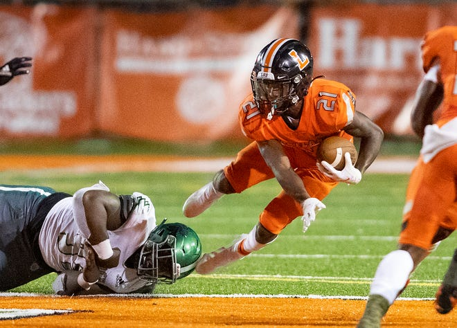 Lakeland Dreadnaughts Reggie Kellum (21) is tackled by Venice's Riley Cleary  (99) during the first half in Lakeland on Friday.