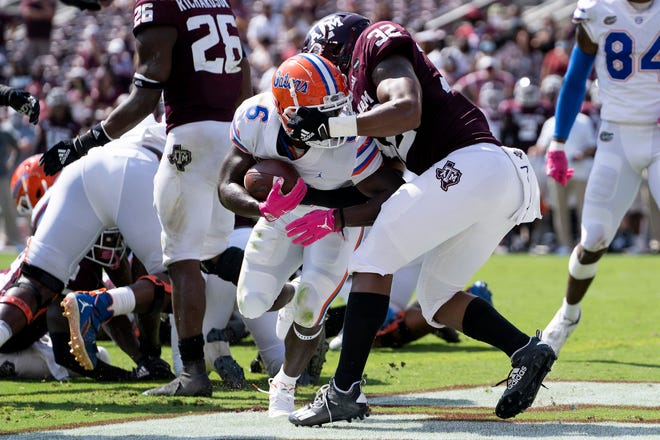 Florida running back Nay'Quan Wright (6) fights his way past Texas A&M linebacker Andre White Jr. (32) for a touchdown during the second quarter in College Station, Texas.