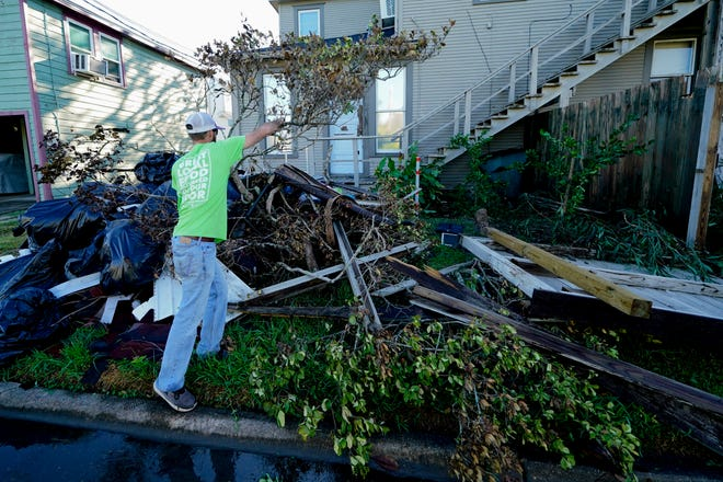 Caleb Cormier moves debris Saturday after Hurricane Delta moved through in Lake Charles, La. Delta hit as a Category 2 hurricane with top winds of 100 mph (155 kph) before rapidly weakening over land.