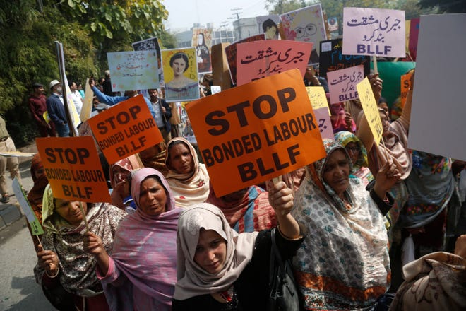 Pakistani activists take part in an International Women's Day rally in Lahore, Pakistan, in March.  A new report on Friday estimates that 29 million women and girls are victims of modern slavery, exploited by practices including forced labor, forced marriage, debt-bondage and domestic servitude.