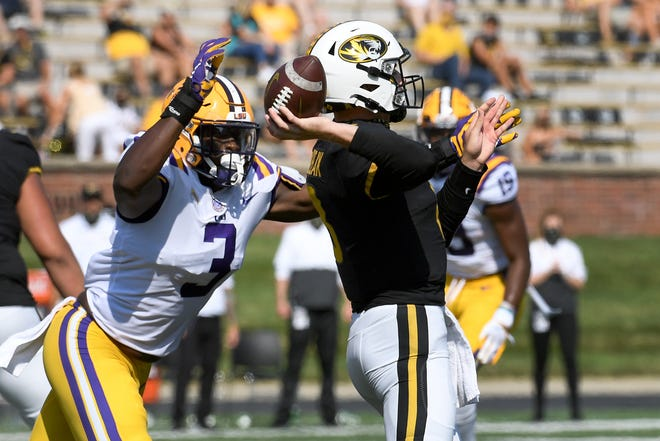 Missouri quarterback Connor Bazelak, right, throws under pressure from LSU offensive lineman Andre Anthony (3) during the first half in Columbia, Mo.