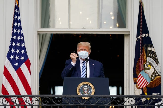 President Donald Trump removes his face mask to speak from the Blue Room Balcony of the White House to a crowd of supporters Saturday.