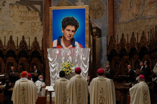 An image of 15-year-old Carlo Acutis, an Italian boy who died in 2006 of leukemia, is unveiled during his beatification ceremony celebrated by Cardinal Agostino Vallini in the St. Francis Basilica, in Assisi, Italy, on Saturday.