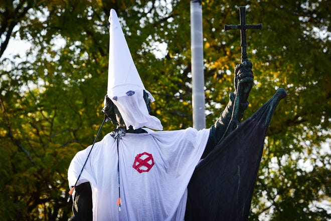 Demonstrators put a KKK cloak and hood on the Christopher Columbus statue on Memorial Parkway in Utica on Saturday, Oct. 10, 2020.