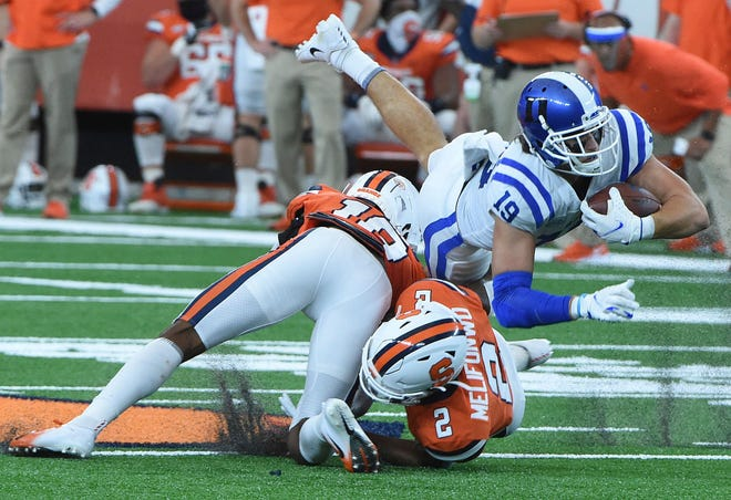 Duke wide receiver Jake Bobo (19) dives for extra yardage against Syracuse's Ifeatu Melifonwu (2) and another player during a game at Saturday at the dome. Duke won 38-24. [Dennis Nett / AP via The Post-Standard]