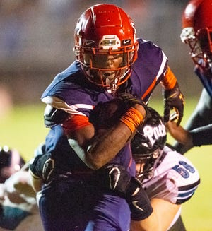 Vanguard's Tyrell Randall tries to elude West Port's William Cotney in the first half. The Vanguard Knights defeated the West Port Wolf Pack 43-6 Friday night.