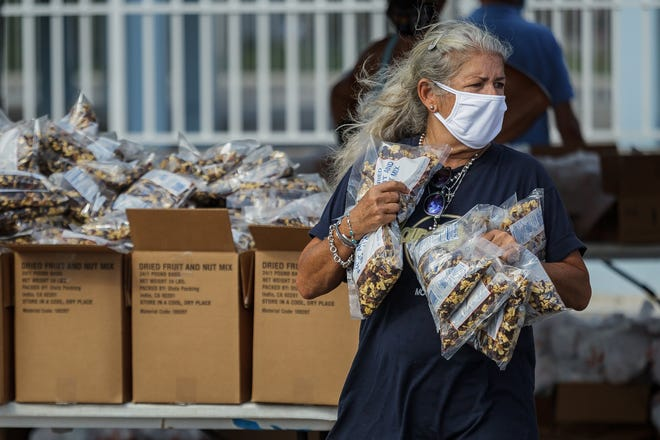 Sonia Barraza, of Lake Worth Beach, distributes food packs Tuesday at a drive-thru Feeding South Florida event at the Hatch 1121 Building in Lake Worth Beach. Dozens of cars queued on eastbound Lake Avenue to pick up groceries.