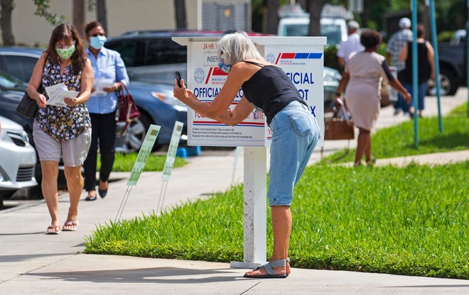 Janet Serrano of Lake Worth Beach takes a selfie for Facebook while she casts her ballot at a dropbox Oct. 5 outside the Palm Beach County Supervisor of Elections Office on Military Trail near Gun Club Road in West Palm Beach.