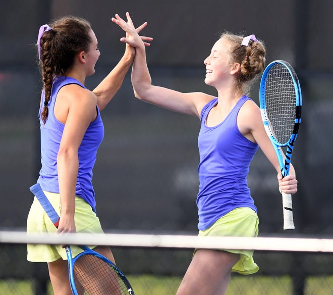 Jackson's Paige Reese (left) and Madison Altman celebrate a win against Hoover's Angelina Koinoglou and Izzy Warburton in Girls tennis Division I Sectional Semifinal at Jackson North Park Saturday, Oct. 10, 2020.