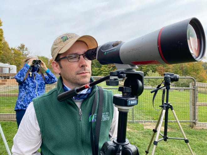 "Adam Zorn, program manager of the Huston-Brumbaugh Nature Center in Washington Township in Stark County, peers through a spotting scope on Saturday as part of ""The Big Sit!,"" an international birdwatching event."