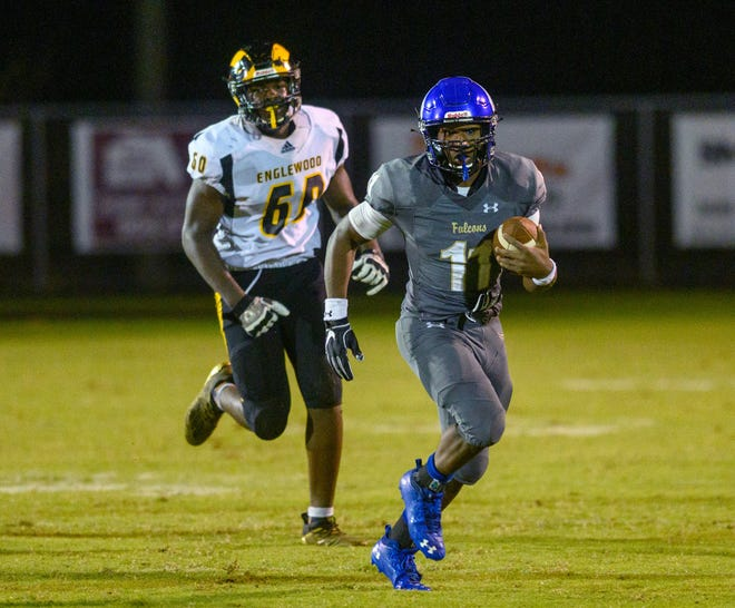 Menendez quarterback King Benford carries the ball in a high school football game against Englewood in October. Benford announced his commitment to Navy football.