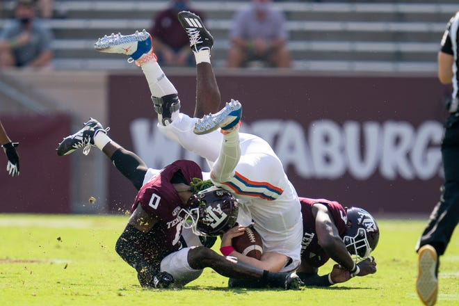 Florida quarterback Kyle Trask is tackled after a short gain by Texas A&M defensive lineman Tyree Johnson (3) and defensive back Myles Jones (0) during the first quarter Saturday in College Station, Texas.