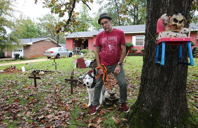 Christopher Lynn and his dog Gallifrey stand with the halloween yard display he created at his home on 36th Ave. East in Tuscaloosa Saturday, Oct. 10, 2020. [Staff Photo/Gary Cosby Jr.]