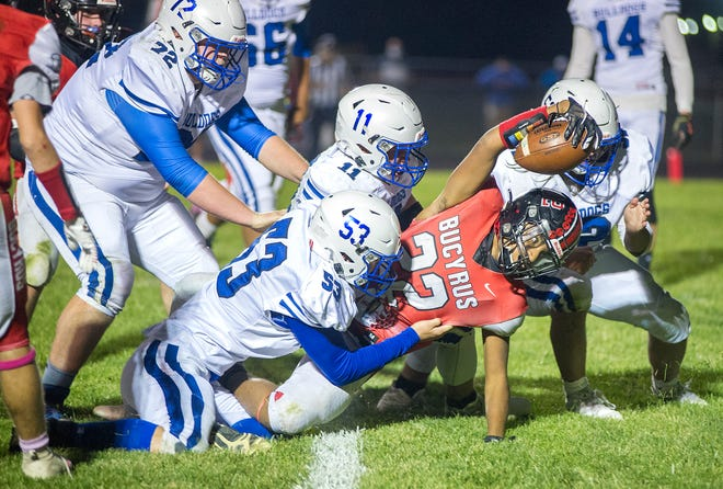 Bucyrus' Eddie Dagher is tackled by Crestline's Jake Bruce and Calvin Reed near the endzone.