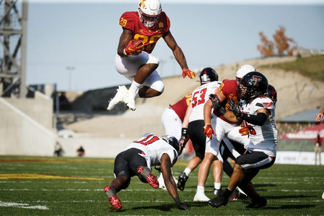 Oct 10, 2020; Ames, Iowa, USA; Iowa State running back Breece Hall (28) jumps over Texas Tech senior defensive back Eric Monroe  (11) during their football game at Jack Trice Stadium. Mandatory Credit: Brian Powers-USA TODAY Sports.