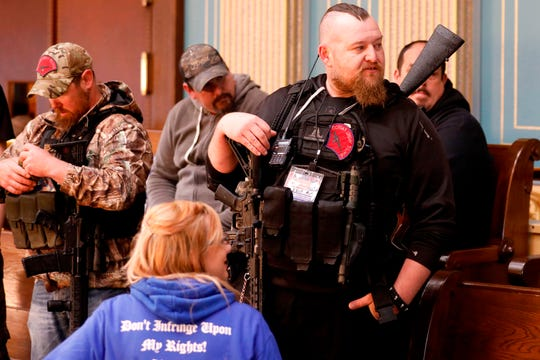 William Null, right, stands in the gallery of the Michigan Senate Chamber during the American Patriot Rally, organized by Michigan United for Liberty, to demand the reopening of businesses on the steps of the Michigan State Capitol in Lansing, Michigan, on April 30, 2020. He was charged in an alleged kidnapping plot that may have included plans to harm the governor.