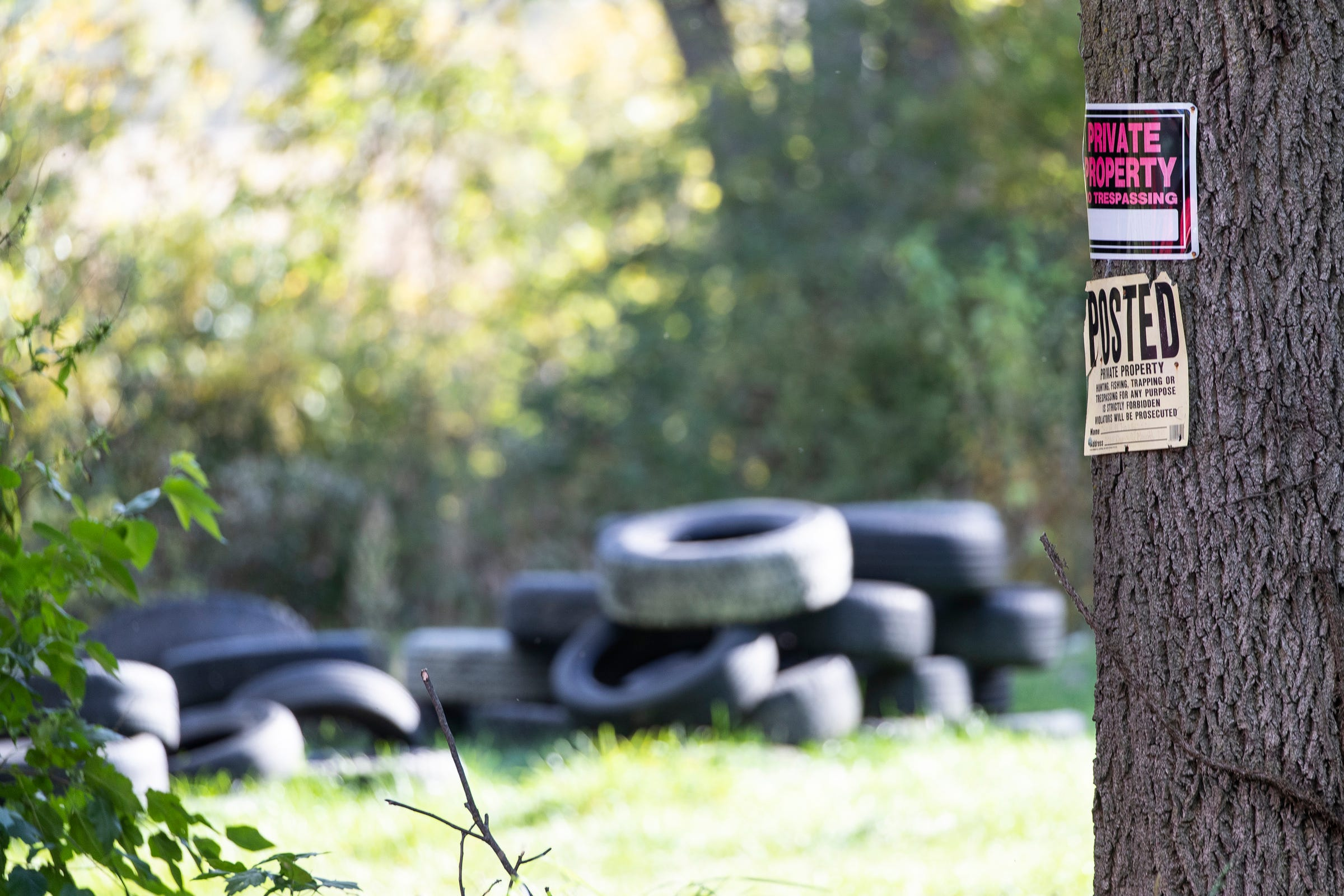 Private property signs are seen in front of a wall of tires on a property where two suspects are believed to reside on Dunn Road in Munith, Thursday, Oct. 8, 2020.