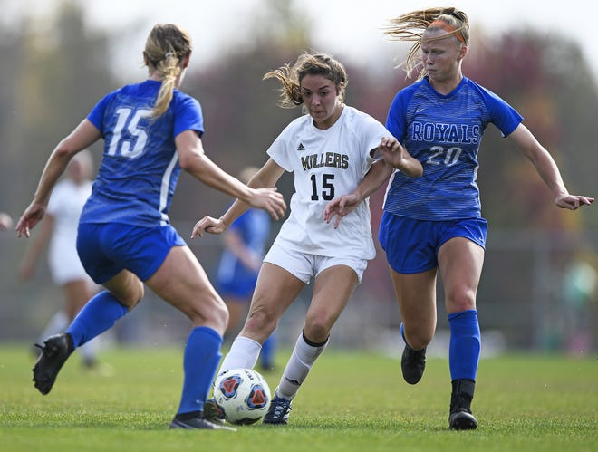 Noblesville Millers Makenna Maloy (15) carries the ball between Hamilton Southeastern Royals Brooke Baker (15) and Caroline Kelley (20) during the sectional final game held in Noblesville, Indiana, on Saturday, Oct. 10, 2020. The Noblesville Millers defeated the Hamilton Southeastern Royals 2-1.