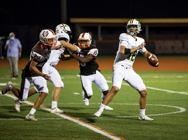 St. X quarterback Giles Pooler (12) rares back to pass during first half action against the DeSales Colts Friday night at Paul B. Cox Stadium. Oct. 9, 2020