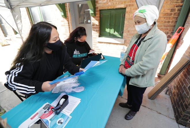 Abby Yang, left, with the Hmong American Women's Association,  and volunteer, Leilonie Lee, center, work with Mu Kwee in providing her with election materials at the Hmong American Women's Association on West National Avenue in Milwaukee on Oct. 10.