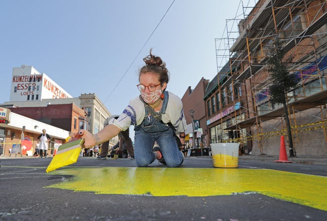 "Kate Stolz of Milwaukee paints a sign that will read ""voting is power"" on Historic Mitchell Street during the Voces de la Frontera Action Black and Brown Lives Matter and voter registration event in Milwaukee on Saturday. The event's aim was to raise awareness about the electoral power of Wisconsin's Latinx and immigrant communities."
