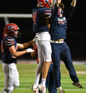 Patriot Don Ufferman celebrates his interception with a Franklin High coaching staff member.