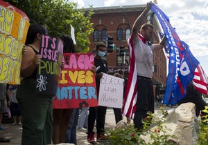 A counter protester (right) stands in front of those in support of the Black Lives Matter movement (left) at the Courthouse Plaza in Prescott, Ariz. on Sept. 4, 2020.