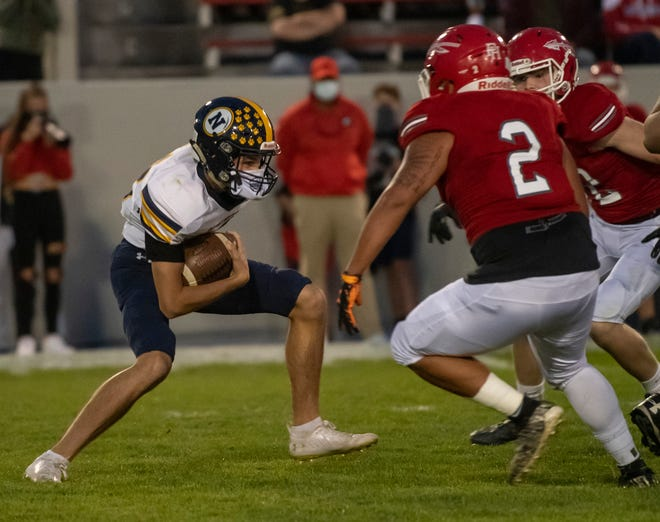 Port Huron Northern's Dylan Boink looks for a hole as two Port Huron defenders close in during their Crosstown Showdown game last season at Memorial Stadium. The two teams, who are both unbeaten in the Macomb Area Conference Blue division, meet again with the Blue title on the line Friday.