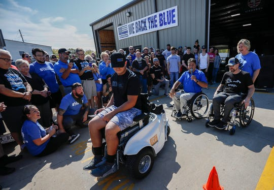 Springfield Police Officer Mark Priebe, right, watches as his son Conner Priebe, 15, drives his new Paramobile during the Priebe Strength Carnival at the Lift Barbell Club in Nixa, Mo., on Saturday, Oct. 10, 2020.