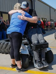 Springfield Police Officer Mark Priebe hugs his wife Heather Priebe after standing up in his Paramobile for the first time during the Priebe Strength Carnival at the Lift Barbell Club in Nixa, Mo., on Saturday, Oct. 10, 2020.