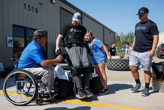 Anthony Netto, left, founder of the Stand Up and Play Foundation, instructs Springfield Police Officer Mark Priebe on how to use his new Paramobile as his daughter Chloe Priebe, 9, gives him a hug and Conner Priebe, 15, watches during the Priebe Strength Carnival at the Lift Barbell Club in Nixa, Mo., on Saturday, Oct. 10, 2020.