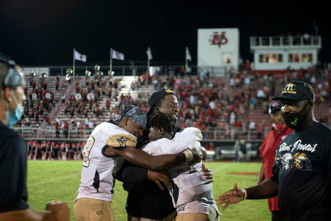Treasure Coast head coach Irvin Jones (center) is embraced by Titans running back Eden James and quarterback Turk Watkins following their 17-16 win against Vero Beach on Friday, Oct. 9, 2020, at the Citrus Bowl in Vero Beach.