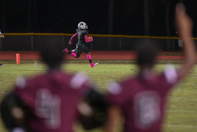 Fort Pierce Westwood's Roddrick Huntley (Center) sprints into the end zone to score on an interception in the 3rd quarter against Okeechobee, as his teammates cheer him on, at Lawnwood Stadium on Friday, Oct. 9, 2020, in Fort Pierce. Fort Pierce Westwood won over Okeechobee, 19-12.