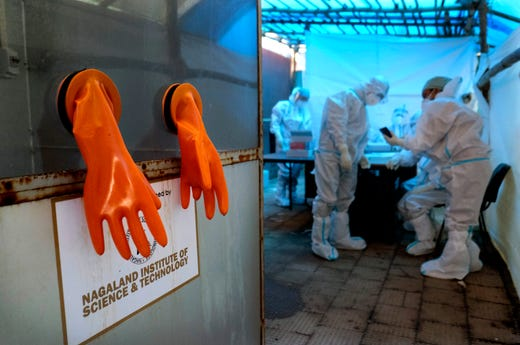 A pair of protective gloves hang by the testing booth, as health workers prepare for the day at a COVID-19 testing center in Kohima, capital of the northeastern Indian state of Nagaland, Saturday, Oct. 10, 2020.