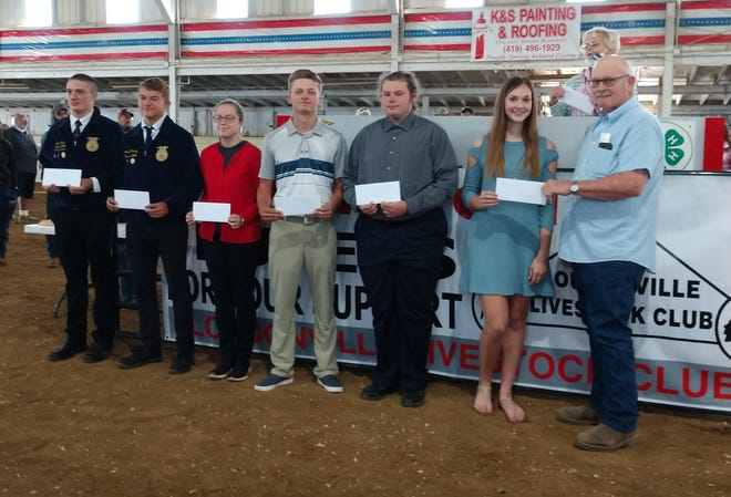 Showing off the Kettering Scholarship checks presented Saturday by Fair Board President Sam Adams, right, are, from left, Grant Portz, Josh Rhamey, Leighann Cutlip, Owen Hinkle, Joel Rucker and Grace Vermilya. Not present was fellow scholarship winner Sidney Snyder.