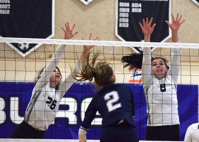Hudson middle hitter Rylyn Dearstine puts down a kill between Twinsburg's Alaina Varga (26) and Ashley Cavadas (8) during the Explorers' 25-10, 25-18, 25-9 win at Twinsburg Oct. 8.