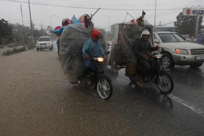 Men drive their motorbikes loaded with goods along a flooded main road during the heavy raining on the outskirts of Phnom Penh , Cambodia, on Sunday. Flooding in Cambodia has killed at least 11 people since the beginning of the month, a disaster official said Sunday.