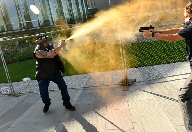 """A man sprays mace, left, as another man fatally fires a gun, Saturday in Denver. The man on the left side of the photo was supporting the """"Patriot Rally"""" and sprayed mace at the man on the right side of the image. The man at right, then shot and killed the protester. The private security guard working for a TV station was in custody Saturday after a person died from a shooting that took place during dueling protests in downtown Denver, the Denver Post reported."""