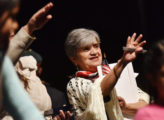 In this November 2019 file photo, Maria Teresa Rojas waves to the audience during a naturalization ceremony at Mohawk Valley Community College in Utica.