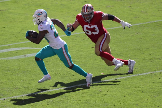Miami Dolphins cornerback Xavien Howard, left, runs against San Francisco 49ers center Ben Garland (63) after intercepting a pass during the first half of an NFL football game in Santa Clara, Calif., Sunday, Oct. 11, 2020.