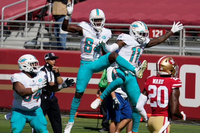 Miami Dolphins wide receiver DeVante Parker (11) celebrates after scoring against the San Francisco 49ers with wide receiver Isaiah Ford (84) and defensive tackle Christian Wilkins (94) during the first half of an NFL football game in Santa Clara, Calif., Sunday, Oct. 11, 2020. Also pictured at right is 49ers free safety Jimmie Ward (20).