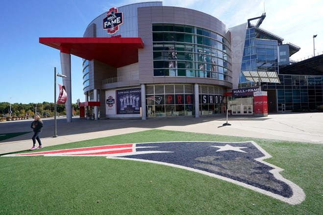 A passer-by walks past a New England Patriots football team logo near the Patriots ProShop at Gillette Stadium, Sunday in Foxborough, Mass. The NFL has postponed the Denver Broncos-New England Patriots game due to another positive coronavirus test with the Patriots.