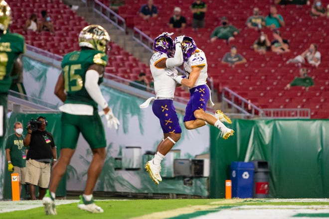 East Carolina Pirates wide receiver C.J. Johnson (5) celebrates Saturday with wide receiver Tyler Snead (22) after scoring a touchdown during the first quarter of a game against the South Florida Bulls at Raymond James Stadium.