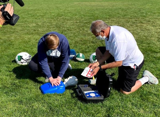 Liberty Point International eighth grader Carson Middleton, left, and HeartSmart Inc. founder Richard Perse work with the AED unit.