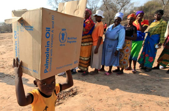 In this Sept. 9, 2015 file photo, a child carries a parcel from the United Nations World Food Program (WFP) in Mwenezi, Zimbabwe.