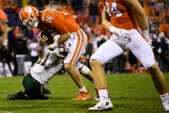 Clemson quarterback Trevor Lawrence (16) is tackled by Miami safety Bubba Bolden (21) during the third quarter of the game against Miami on Saturday at Memorial Stadium in Clemson, South Carolina.