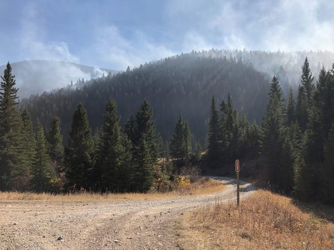 The Yogo Fire kicks up smoke near Morris Creek Saturday, when high winds pushed the fire and pressured fire lines.