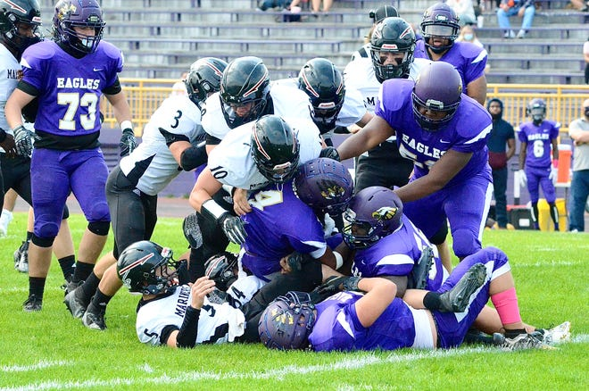 Marine City's Defense gets a group tackle during a Macomb Area Conference-Silver football game on Saturday, Oct. 10, 2020, at Madison Heights Madison.